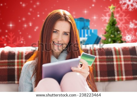 Woman shopping online against christmas tree with gifts