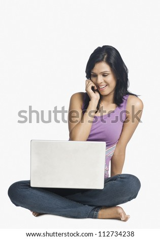 Woman shopping online and talking on a mobile phone - stock photo