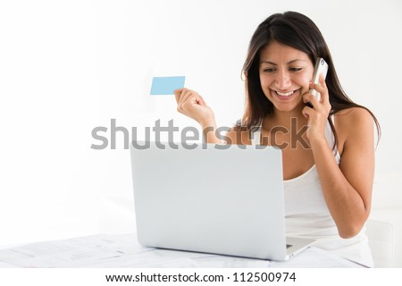 Woman shopping online from home and talking on the phone - stock photo