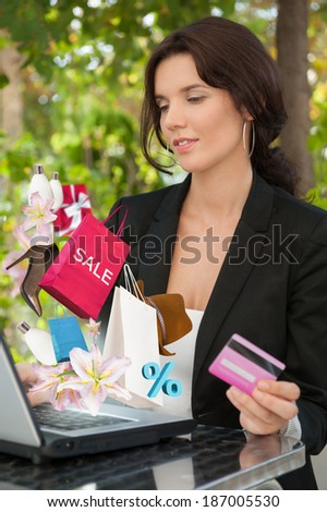 Woman shopping online using her laptop and credit card outdoors at summer park