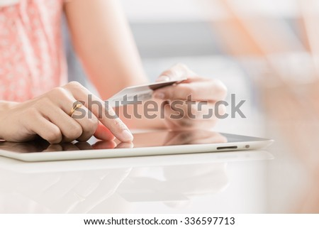 Woman shopping using tablet pc and credit card