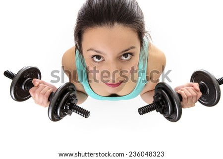 Woman shot from a birds eye view looking down lifting dumbbells weight and in training