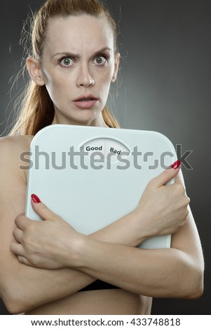 woman shot in the studio, low key lighting holding weight scales with the words Good bad printed on the scales disk - stock photo