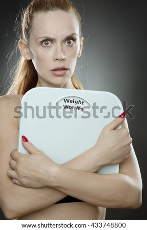 woman shot in the studio, low key lighting holding weight scales with the words weight worries on the scales
