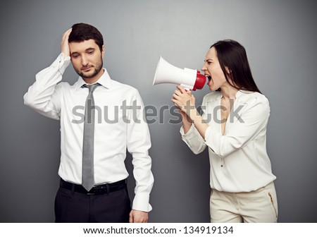 woman shouting in megaphone at the tired man. studio shot over dark background - stock photo