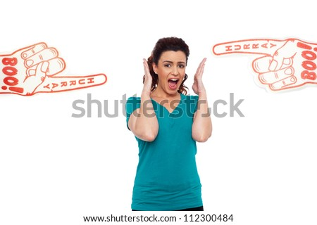 Woman shouting loud, stuck in between two large hurray boo foam hands pointing at her - stock photo