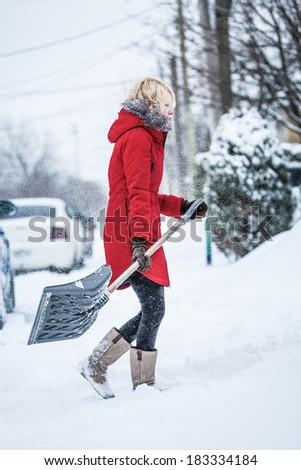 Woman Shoveling her Parking Lot after a Snowstorm - stock photo