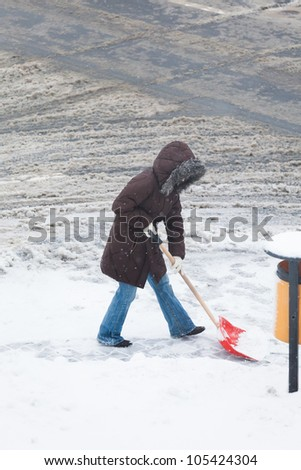 Woman shoveling snow - stock photo