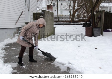 Woman shoveling snow off