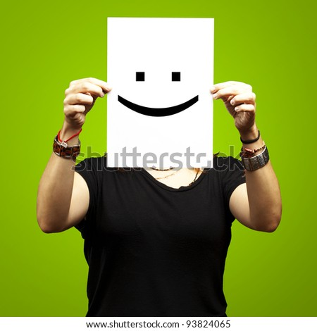 Woman showing a blank paper with a smile emoticon in front of her face against a green background