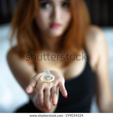 Woman showing a condom on bed, Focus on the condom in the foreground - stock photo