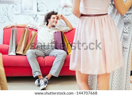 Woman showing a dress she wants to buy to her boyfriend. - stock photo