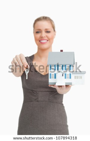Woman showing a key and a model house against white background - stock photo