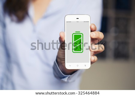 Woman showing a mobile phone with full battery icon in the screen. - stock photo