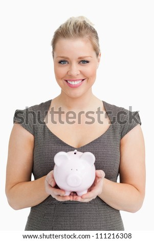 Woman showing a pink piggy bank against white background