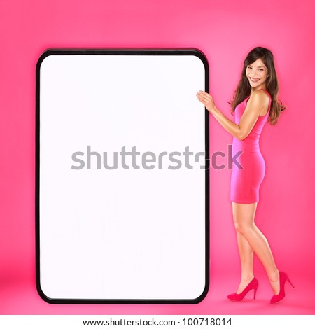 Woman showing big sign. Beautiful happy sexy young woman in pink dress holding big blank empty sign board with copy space. Mixed race Asian / Caucasian female fashion model on pink background. - stock photo