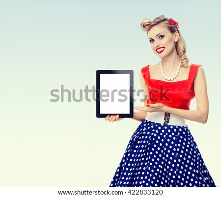 woman, showing blank no-name tablet pc monitor, with copyspace, dressed in pin-up style dress in polka dot. Caucasian blond model posing in retro fashion vintage shoot. - stock photo