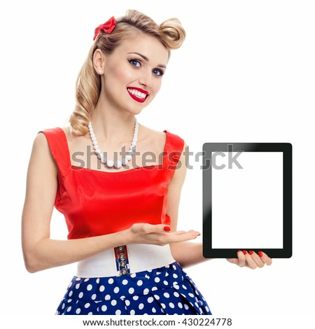 Woman, showing blank no-name tablet pc monitor, with copyspace, dressed in pin-up style dress in polka dot, isolated on white. Caucasian blond model posing in retro fashion vintage shoot. - stock photo