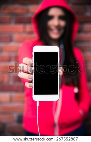 Woman showing blank smartphone display over brick wall. Focus on smartphone
