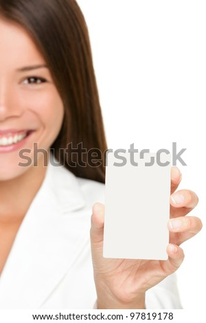 Woman showing business card. Businesswoman in suit holding blank card sign. Can be replaced with mobile phone or smart phone. Mixed race Asian / Caucasian business woman on white background in suit. - stock photo
