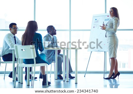 Woman showing financial charts to her colleagues - stock photo