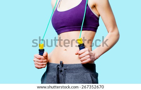 Woman showing her abs with jumping-rope after weight loss on blue background - stock photo