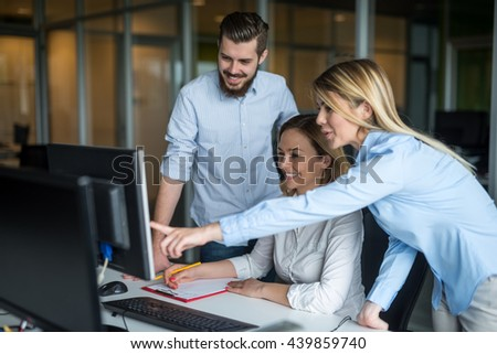 Woman showing her colleagues something on a computer. - stock photo