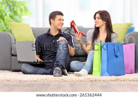 Woman showing her new shoes to boyfriend at home  - stock photo