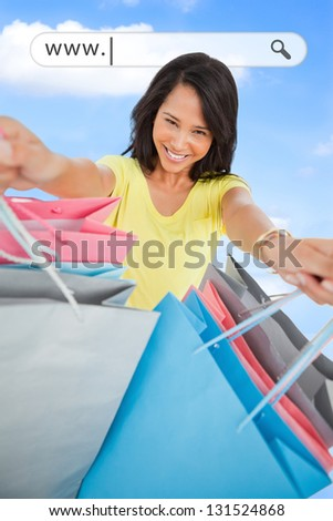 Woman showing her shopping bags under address bar on blue sky background - stock photo