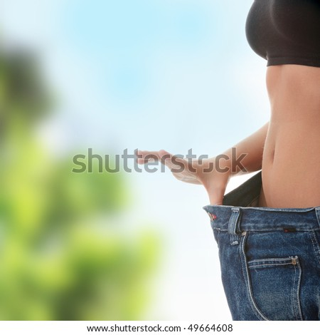 Woman showing how much weight she lost. Healthy lifestyles concept - stock photo