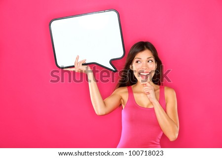 Woman showing sign speech bubble banner looking happy excited on pink background. Beautiful young multiracial Caucasian / Asian Chinese joyful model on pink background having idea.