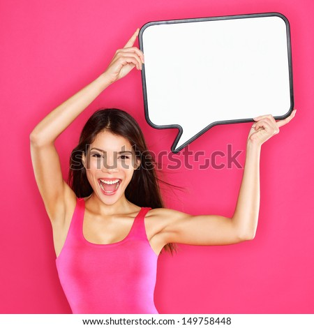 Woman showing sign speech bubble happy sexy with copy space for text. Beautiful excited smiling joyful mixed race Asian / Caucasian female fashion model in pink dress on pink background. Energetic. - stock photo