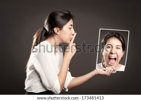 woman showing silence gesture and holding a portrait of herself