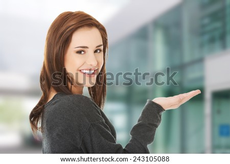 Woman showing something on copyspace for product - stock photo