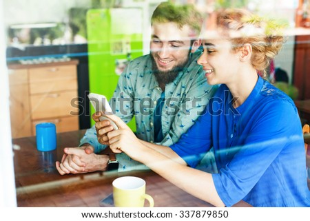 woman showing something on her smart phone to man in cafe - stock photo