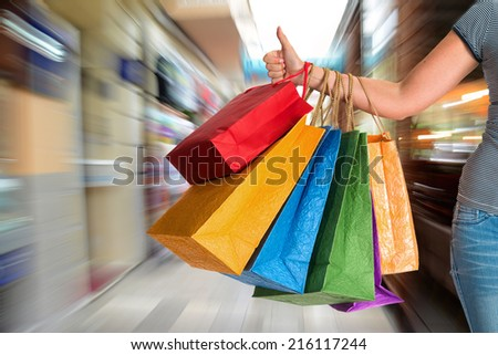 Woman showing thumb up and holding shopping bags at shopping mall
