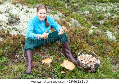 Woman showing thumb when sitting near full mushroom basket - stock photo