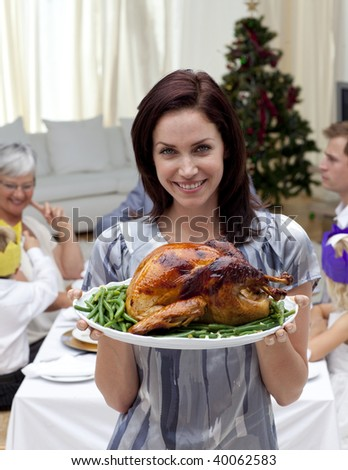Woman showing to the camera Christmas turkey for dinner