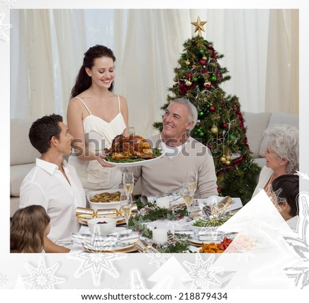 Woman showing turkey to her family for Christmas against christmas frame