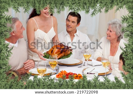 Woman showing turkey to her family for Christmas dinner against green fir branches - stock photo