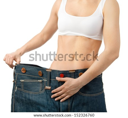 woman shows her weight loss by wearing an old jeans, isolated on white background - stock photo
