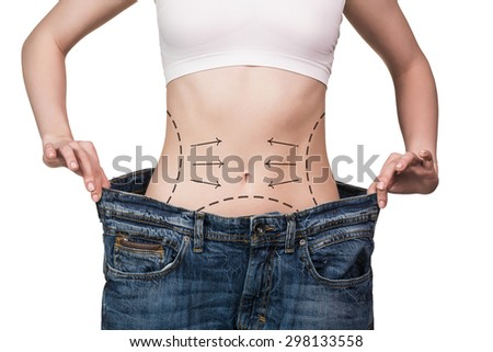 Woman shows her weight loss. Isolated on white background - stock photo