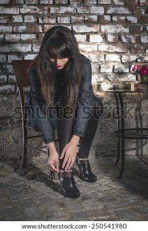 Woman shows hers shoes. Vintage brick wall. Bulgaria