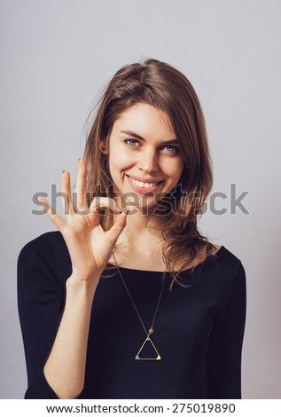 Woman shows okay on a gray background. - stock photo