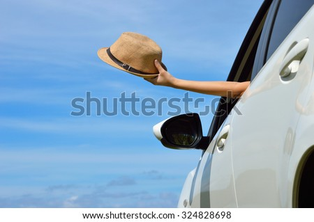 Woman shows sun hat from car window - stock photo