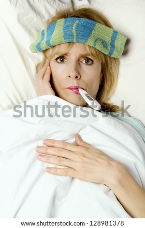 Woman sick in bed or hospital with thermometer in mouth  and washcloth on face - stock photo
