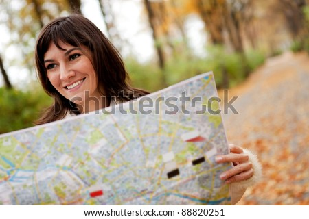 Woman sightseeing outdoors and holding a map - stock photo