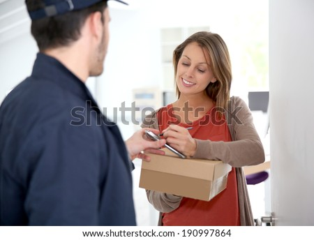 Woman sigining electronic receipt of delivered package  - stock photo