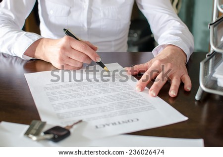 Woman signing a car purchase contract in car dealership - stock photo