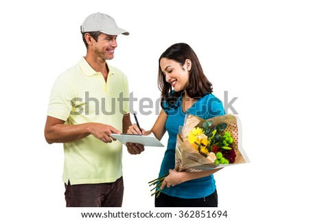 Woman signing on clipboard while receiving bouquet against white background - stock photo